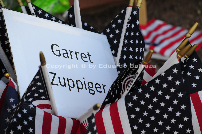 Phoenix, Arizona. July 3, 2013. A small makeshift memorial for the 19 Arizona firefighters who died on June 30 battling the Yarnell Hill wildfire was built outside the Forensic Science Center in Phoenix, where autopsies are being conducted. A sign written by Captain Albert Bandin honors the 19 members of the Granite Mountain Hotshots team who perished fighting a wildfire in the community of Yarnell, Arizona. The name of fallen firefighter Garret Zuppiger, 27, was printed on a sheet of paper and placed on a container surrounded for many small American flags. Zuppiger is one of the 19 member of an elite firefighting crew who died in the Yarnell Hill fire. Photo by Eduardo Barraza © 2013