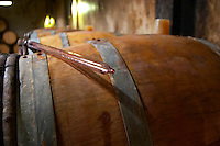 Domaine Clos Marie. Pic St Loup. Languedoc. Barrel cellar. Drawing a sample with a pipette. France. Europe.