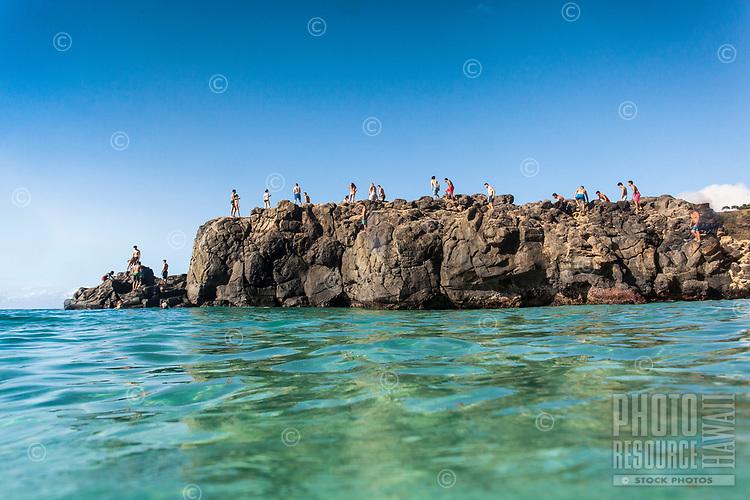 Beachgoers walk on the famous (and dangerous) Jump Rock at Waimea Bay, O'ahu.