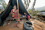 Hari Maya Bhujel sits in her tent while her grandson, 5-year old Utsab, does his school homework in Majhitar, a village in the Dhading District of Nepal. The woman is living in the tent pending the construction of a permanent replacement dwelling.<br /> <br /> Parental consent obtained.