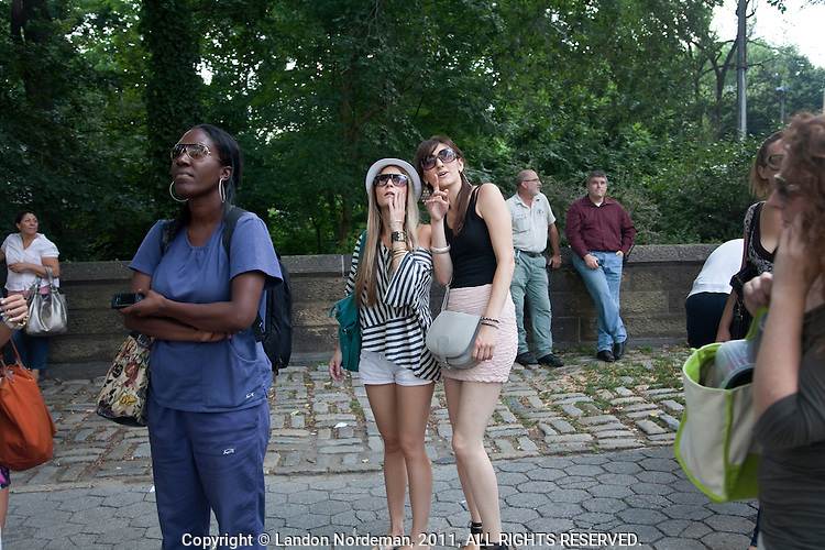 Women on the street observe a male peacock that escaped from the Cenral Park Zoo as it perches on a 5th floor window ledge at 838 5th Avenue in New York City on Tuesday, August 2 2011