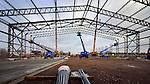 SCHIPHOL - Bij Schiphol monteren medewerkers van Aa-Dee Machinefabriek Staalbouw Nederland uit Schijndel de stalen spanten van een door Heijmans te bouwen busstation. Op basis van een Engelse T2 vliegtuighangar die na de Tweede Wereldoorlog door Rotterdam The Hague Airport werd gekocht, verrijst een 100 meter lange en 37 meter brede overkapping. Het project waarin tevens de bouw van een chauffeursloge, een glazen wachtruimte, windschermen, banken en een fietsenstalling wordt opgenomen, kost elf miljoen euro, en is gefinancierd door de Stadsregio Amsterdam, Schiphol Group, Provincie Noord Holland en gemeente Haarlemmermeer. De Engelse spanten zijn te herkennen aan de roodbruinen kleur. COPYRIGHT TON BORSBOOM