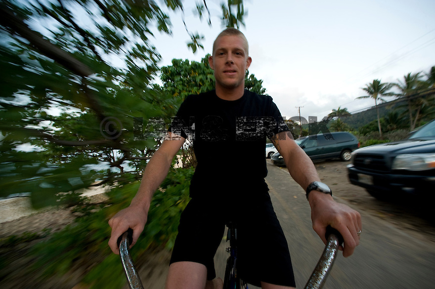 Mick Fanning riding the Joli's bike on the parth at Sunset Beach on the Northshore of Oahu in Hawaii.
