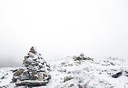 Snow covered rock cairn during the winter months on the summit of Bondcliff Mountain in the Pemigewasset Wilderness in the New Hampshire White Mountains.