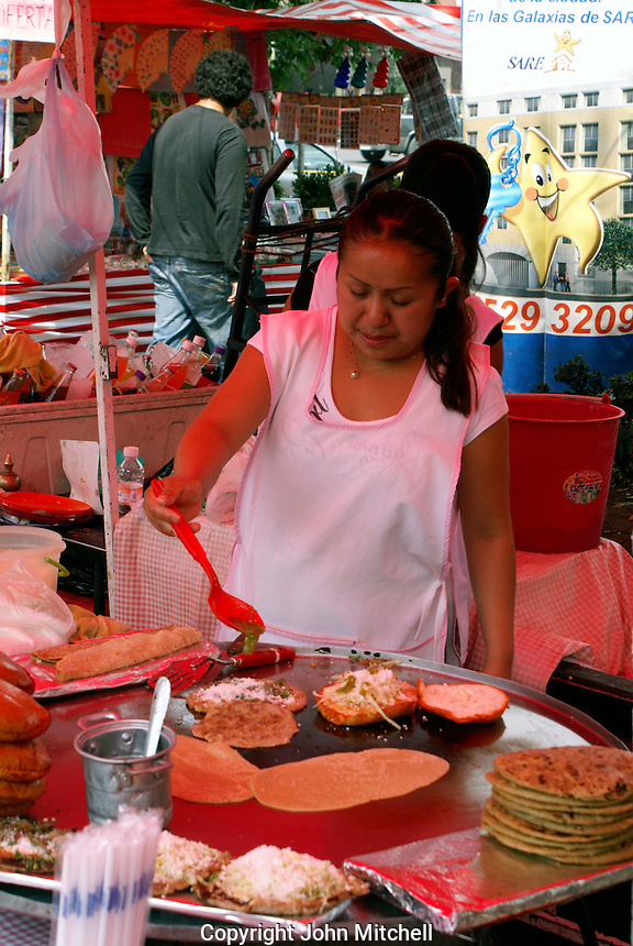 Woman cooking Mexican food at a sidewalk food stall in Mexico City
