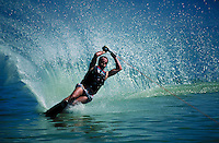 A waterskier lays over in a turn and sprays a wall of water. sports. Brad Bateman. Utah, Utah Lake.