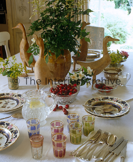 The dining table has a floral centrepiece guarded by four wooden ducks