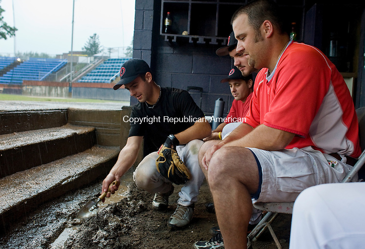 TORRINGTON--2 August 08--080208TJ04 - Oakville player Kyle Tehan, left, digs a trough for rainwater as coach Tim Belcher, from right, player Jay Spear, and head coach Scott Ouellette wait out a rain storm before their round one game is postponed in the American Legion tournament, at Fuessenich Park on Saturday, August 2, 2008. (T.J. Kirkpatrick/Republican-American)