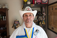 "Carlos Arredondo, 57, poses for a picture at his home in Roslindale, Boston, Massachusetts, USA, on Sat., March 31, 2018. Arredondo is well known as the ""man in the cowboy hat"" who helped out in the aftermath of the Boston Marathon Bombing in 2013. Carlos is wearing a jacket that he has used to create a t-shirt design for when he runs the Boston Marathon later this year. Though he has run the race unofficially previously, this will be the first time he runs it ""legally,"" he says."