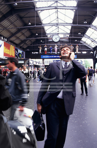 Zurich, Switzerland. Businessman in suit talking on a mobile phone; railway station.