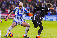 Crystal Palace's midfielder Wilfried Zaha (11) flicks the ball by Huddersfield Town's forward Aaron Mooy (10) during the EPL - Premier League match between Huddersfield Town and Crystal Palace at the John Smith's Stadium, Huddersfield, England on 17 March 2018. Photo by Stephen Buckley / PRiME Media Images.
