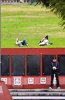 Monument commemorating the Falkland war Islas Malvinas on the Plaza San Martin Square, black marble plaques with names engraved of the soldiers in the war on red stone background, map of the island, two military honour guards in a park. young people sleeping on the grass behind. the Plaza San Martin Square renamed Plaza de la Fuerza Aerea or Plaza Fuerza Retiro Buenos Aires Argentina, South America