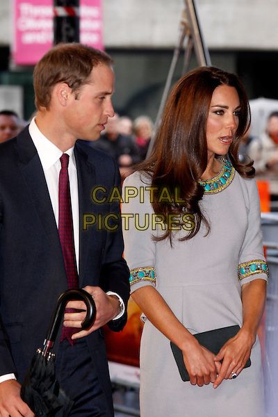 Prince William, Duke of Cambridge and Catherine, Duchess of Cambridge.'African Cats' UK Premiere at BFI Southbank, London, England..25th April 2012.half length kate royals royalty married husband wife blue suit grey gray dress turquoise gold beads beaded mouth open profile clutch bag.CAP/AH.©Adam Houghton/Capital Pictures.