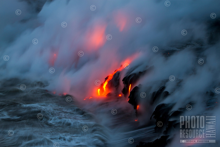 Lava flows into the ocean as waves break against and cool the new land created between Kalapana and Hawai'i Volcanoes National Park, Big Island.