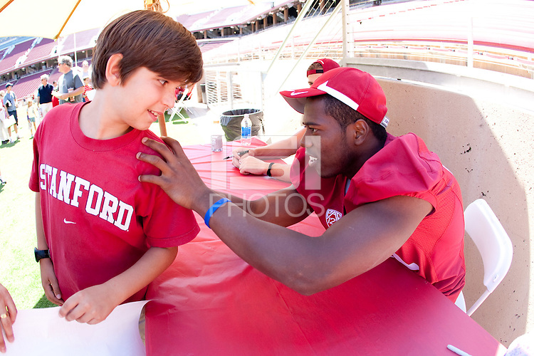 STANFORD CA - August 21, 2011: Chris Owusu signs autograph at the Stanford Cardinal Football Open House took place Sunday, August 21, 2011 at Stanford Stadium. <br /> <br /> Youngsters got to practice at skills stations run by Stanford Football coaches. Fans of all ages were able to watch the 2011 squad practice, get autographs from their favorite players, and have their pictures taken with the 2011 Orange Bowl Trophy.