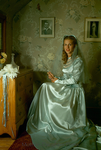 Young woman prepares for her wedding in her bedroom full of sentimental items and a photo of her fiance