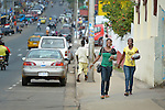 Isabella Washington (left), 26, and Catherine Hill, 28, walk along a street in Monrovia, Liberia, after attending class at United Methodist University. Both women are studying with help from scholarships from United Methodist Women.