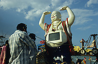 INDIA Tamil Nadu Vellankanni, roman catholic cathedral Our lady of good health is holy pilgrimage place for christians, muslims and hindus, pilgrims on the beach at indian ocean, buddha statue with computer screen / INDIEN Tamil Nadu Vellankanni, die roemisch katholische Kathedrale der Jungfrau Maria ist Pilgerort fuer Christen Hindus Muslime, Wallfahrtsort und Glaube an Wunder, Jahrmarkt und Menschen am Meer, Buddha Figur mit Computer Monitor