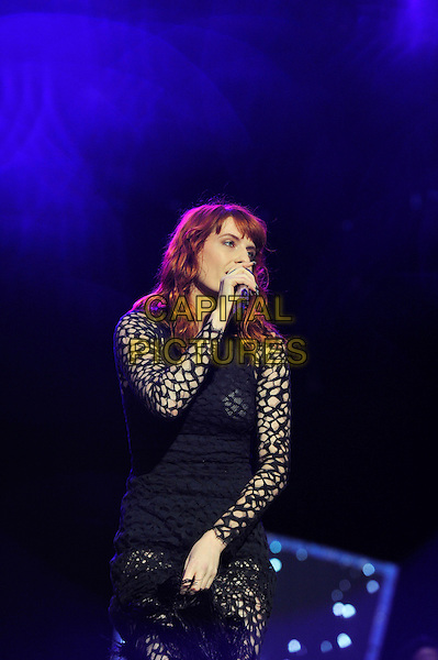 Florence Welch of Florence and the Machine.performing live at Reading Festival, Reading, England, UK,.25th August 2012..half length music concert gig live on stage sheer feathers black dress cut out holes long sleeve microphone singing .CAP/MAR.© Martin Harris/Capital Pictures.