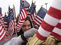 NWA Democrat-Gazette/FLIP PUTTHOFF<br /> PARADE READY<br /> Heaven Day of Gravette, who starts U.S. Army basic training soon, distributes American Flags on Saturday Nov. 11 2017 at the Lowell Veterans Day parade. The group, Remember Everyone Deployed, or Red Friday, organized the parade that traveled south on  Dixieland Road. Red Friday provides support for veterans from the time start basic training into retirement, said Mike Whitehead with Red Friday. Rogers High School Marching Band, military, police and firefighting vehicles and veterans were part of the Saturday morning parade.
