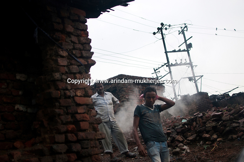 Residents of Indra Chowk. Indra Chowk located at the border of Jharia town is also being affected by the mine fire. Even some 10 years ago the fire hadn't spread to the buildings of the residents like now.  A huge coal mine fire is engulfing the city of Jharia from all its sides. All scientific efforts have gone in vain to stop this raging fire. This fire is affecting lives of people living in and around Jharia. Jharkhand, India. Arindam Mukherjee