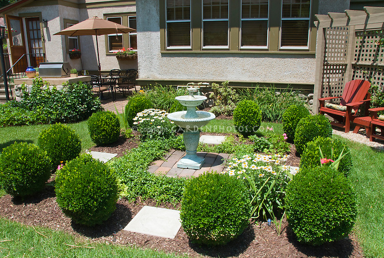 Formal Garden Scene With Clipped Boxwood And Fountain In