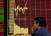 A private investor looks at an electronic board at the stock exchange in Beijing, China. After four years in the doldrums, China's stock markets began to rebound at the beginning of 2006, with the benchmark Shanghai Composite Index almost more than doubling in a year..24 Apr 2007