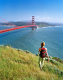 USA, California, Marin Headlands, woman hiking with Golden Gate Bridge and San Francisco in background