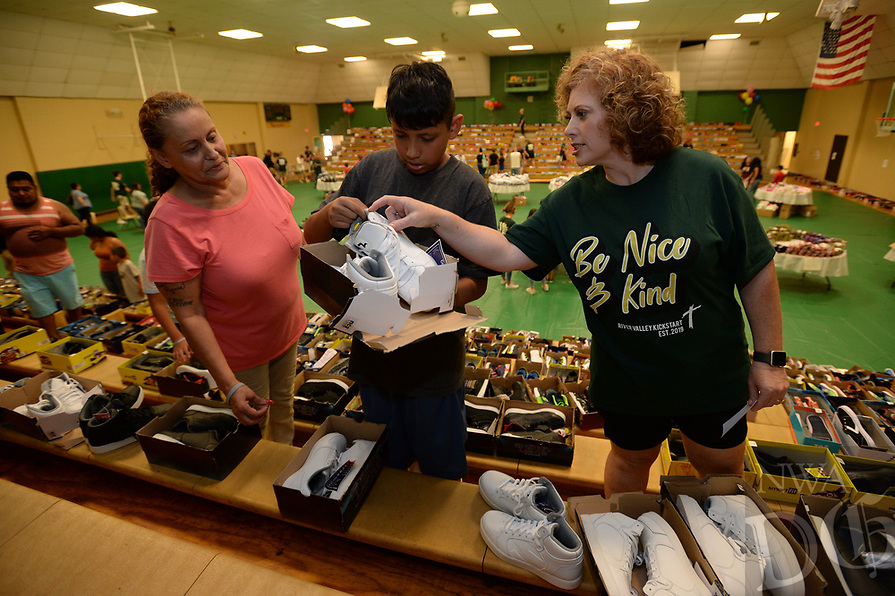 NWA Democrat-Gazette/ANDY SHUPE<br /> Volunteer Annecia Fort (right) helps Isaac Duran, 13, of Van Buren to pick out a new pair of shoes as his grandmother, Charlene Duran, helps Saturday, Aug. 10, 2019, during the River Valley Kick Start at Alma Middle School. Inspired by her daughter, Harper, attorney Carrie Jernigan bought all 1,500 pairs of shoes from a closing Payless Shoe Source in Fort Smith. Her effort national publicity and thousands of dollars in donations, which she used to buy more shoes and school supplies for kids going back to school.