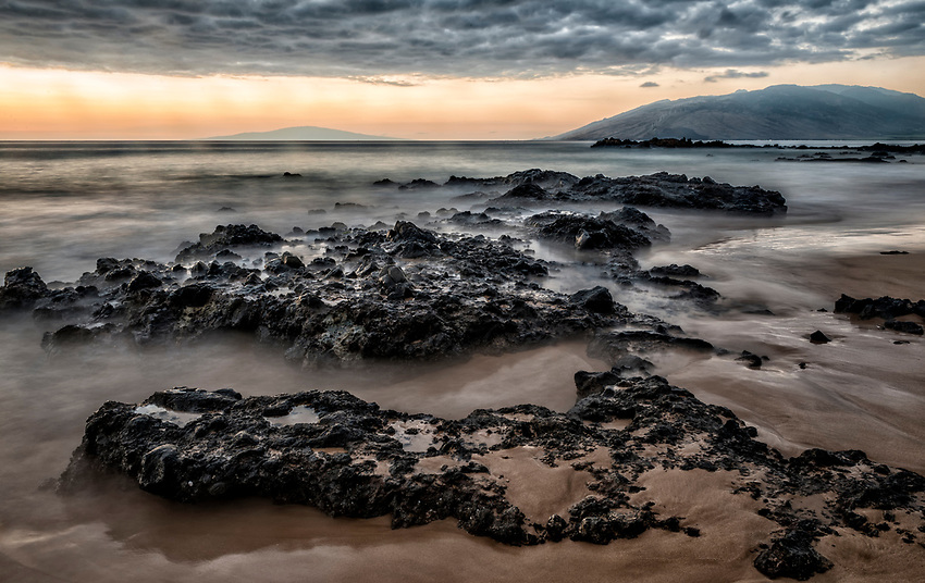 View northwest at dusk from Kamaole Beach III in Kihei, Maui. In the background on the right is West Maui. The island to the left is Lanai.