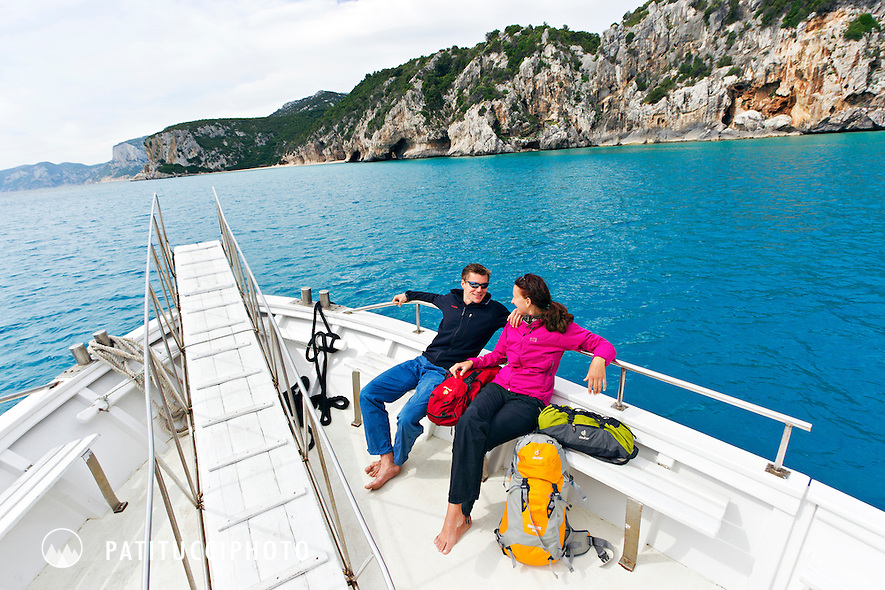 A couple on a powerboat shuttle headed for the climbing in Cala Gonone along the shore of the Mediterranean in Sardinia