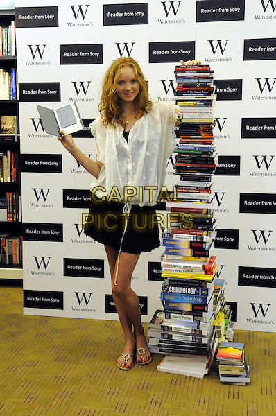 LILY COLE.Launch of the new Sony eReader, Waterstones, Piccadilly, London, England..September 3rd, 2008.book reader electronic gadget ebooks tower books black skirt white blouse top full length .CAP/DH.©David Hitchens/Capital Pictures.