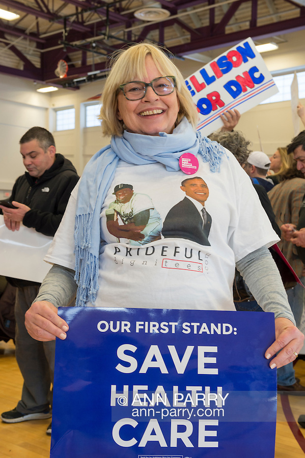 """Westbury, New York, USA. January 15, 2017.  NANCY BERGER, of Merrick, is holding an """"OUR FIRST STAND: SAVE HEALTH CARE"""" poster and wearing a shirt with President Obama's picture on it, at the """"Our First Stand"""" Rally against Republicans repealing the Affordable Care Act, ACA, taking millions of people off health insurance, making massive cuts to Medicaid, and defunding Planned Parenthood. It was one of dozens of nationwide Bernie Sanders' rallies for health care that Sunday."""