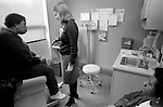 Young seated female internal medicine resident physician talking with middle age African-American female patient on examination table in examination room, patient accompanied by middle-age African-American friend