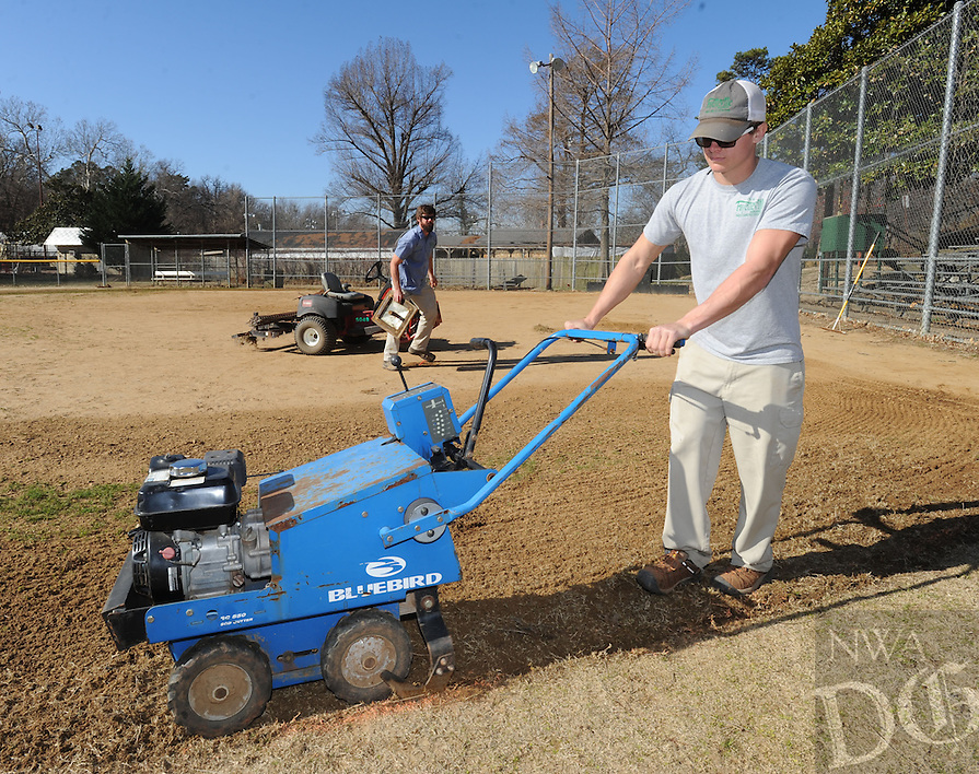 NWA Democrat-Gazette/ANDY SHUPE<br /> C.J. Crowley, a worker with the city of Fayetteville Parks and Recreation Department, uses a sod cutter Wednesday, Feb. 8, 2017, while working to prepare the ball field at Wilson Park for the upcoming season of play. The cutter allows Crowley to remove crabgrass that has grown into the infield and creates a sharp division between infield and outfield.