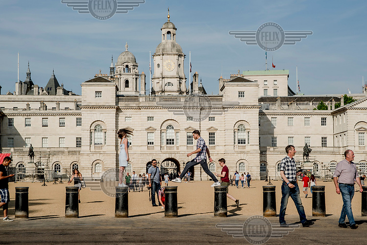 Tourists play on the bollards at Horseguards Parade.