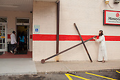 """Dean Padgett parks his cross outside of Los Primos on Alston Avenue before a bathroom break.  """"The greatest sin is doing nothing, it's the greatest selfishness of all,"""" he says."""