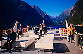 Tourists on a ferry tour of Milford Sound, Fiordland National Park, South Island, New Zealand.