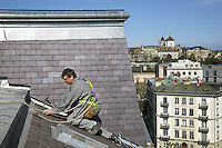 Switzerland. Geneva. A laborer from the company Cerutti Toitures SA is working on a roof in the town center. View on the old town and the St. Pierre Cathedral. The St. Pierre Cathedral is a cathedral which belongs to the Reformed Protestant Church of Geneva. 19.03.2014 © 2014 Didier Ruef