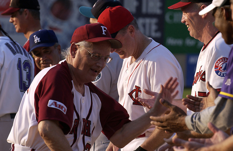 Bill Pascrell gives out high fives to team mates  before the start of the 2004 Congressional Baseball Game.