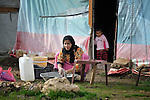 Zahida Al-Mohammed, a woman refugee from Syria, does her laundry in front of her family's makeshift shelter in the village of Jeb Jennine, in Lebanon's Bekaa Valley, where she arrived a month earlier. They and other refugee families in the area are being assisted by International Orthodox Christian Charities and other members of the ACT Alliance..