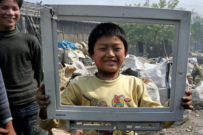 """A migrant child from Henan province holds up a piece of e-trash, once a computer screen bearing a """"Nokia"""" logo in a junk yard in Guiyu in Guangzhou province."""