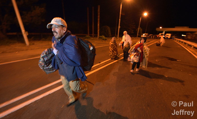 A refugee family from Deir ez-Zor, Syria, crosses from Hungary into Austria at night near the Hungarian town of Hegyeshalom. <br /> <br /> While her husband walks ahead, Mayada Ari follows behind, shepherding her four children. She was a math teacher in Syria. When the fighting caused her eyesight to deteriorate, and she was constantly afraid for her children, she and her husband decided to take their kids and set off for western Europe. &quot;We heard that the best life is in Germany,&quot; she said. They traversed Turkey and Greece and Macedonia and Serbia until arriving in Hungary. She said the journey has been difficult and dangerous. &quot;But it was more dangerous to remain at home,&quot; she said.<br /> <br /> At the border crossing, the family received food and blankets from Hungarian Interchurch Aid, a member of the ACT Alliance. <br /> <br /> Hundreds of thousands of refugees and migrants flowed through Hungary in 2015, on their way to western Europe from Syria, Iraq and other countries.