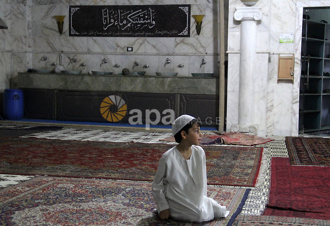 Syrian Muslim worshipers attend Laylat Al Qadr prayers on the 27th day of the holy fasting month of Ramadan at a mosque in al-Kalasa district in the northern Syrian city of Aleppo, on July 13, 2015. Muslims fasting in the month of Ramadan must abstain from food, drink and sex from dawn to dusk, when they break the fast with a meal known as Iftar. Photo by Ameer al-Halbi