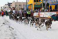 Musher Mike Santos and Iditarider.leave the 2011 Iditarod ceremonial start line in downtown Anchorage, Alaska