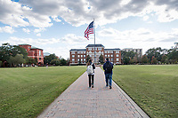 Students walking on Drill Field sidewalk towards Swalm.<br />