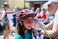 NWA Democrat-Gazette/CHARLIE KAIJO (From right) Cody Navarro of Bentonville puts a flag on Avery Navarro, 9, before a bike ride during the farmer's market, Saturday, July 7, 2018 at the Square in Bentonville. <br />