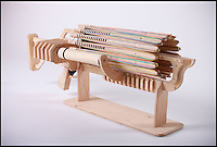 BNPS.co.uk (01202 558833)<br /> Pic: Alex Shpetniy/BNPS<br /> <br /> A student has invented the ultimate boy's toy that promises to be a real blast - because it is a rubber band machine gun.<br /> <br /> The wooden contraption can fire 672 rubber bands a distance of 25 feet at a blistering 14 shots a second from its 16 'barrels', ensuring victory in any office spat.<br /> <br /> It runs off five AA batteries and thanks to its ingenious design it can be reloaded with ammo in a matter of minutes.<br /> <br /> The toy is the brainchild of 18-year-old art and design student Alex Shpetniy who based it on the Gatling gun, one of the world's first rapid-fire weapons.