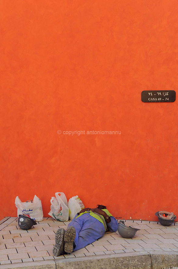 Doha Qatar novembre 2010. Un operaio riposa durante la costruzione dello sviluppo immobiliare The Pearl. Una parte è liberamente ispirata all'architettura di Venezia. Worker at rest during the construction works of the new real estate development The Pearl a part of which is freely inspired  by Venezia's architecture.