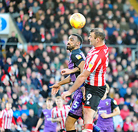Lincoln City's Matt Rhead vies for possession with Port Vale's Leon Legge<br /> <br /> Photographer Andrew Vaughan/CameraSport<br /> <br /> The EFL Sky Bet League Two - Lincoln City v Port Vale - Tuesday 1st January 2019 - Sincil Bank - Lincoln<br /> <br /> World Copyright &copy; 2019 CameraSport. All rights reserved. 43 Linden Ave. Countesthorpe. Leicester. England. LE8 5PG - Tel: +44 (0) 116 277 4147 - admin@camerasport.com - www.camerasport.com